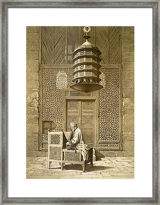 An Imam Reading The Koran In The Mosque Framed Print by Maurice Keating