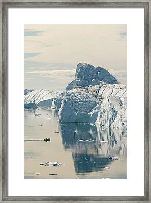An Inuit Fishing Boat In Icebergs Framed Print by Ashley Cooper