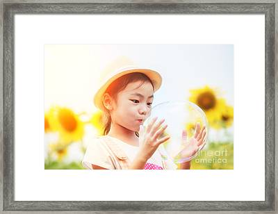 Asian Little Girl Is Blowing A Soap Bubbles In Sunflower Garden Framed Print by Anek Suwannaphoom