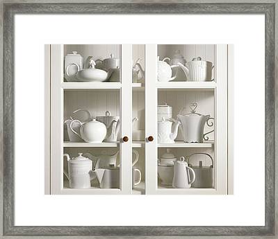 Assorted Tea And Coffee Pots In A Glass Cupboard Framed Print by Sivan Lewin