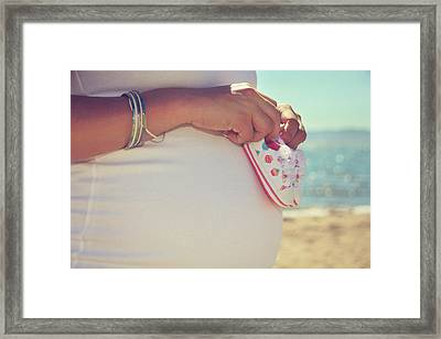 Baby Booties On A Baby Bump On The Beach Framed Print
