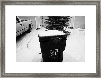bag sticking out of litter waste bin covered in snow outside house in Saskatoon Saskatchewan Canada Framed Print