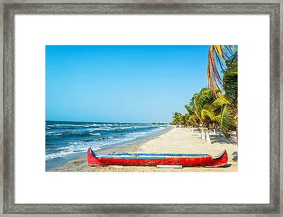 Beach And Red Canoe Framed Print