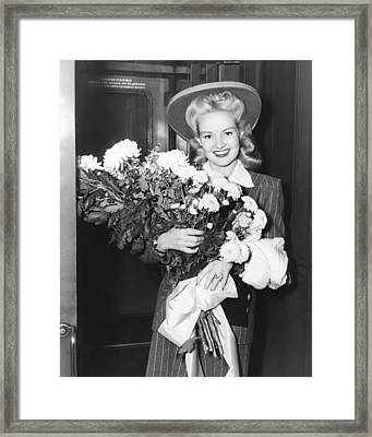 Betty Grable With Flowers Framed Print by Underwood Archives