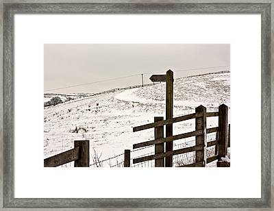 Blank Wooden Signpost On Snow Covered Moorland Framed Print by Ken Biggs