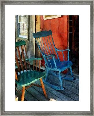 Blue Chair Against Red Door Framed Print by Susan Savad