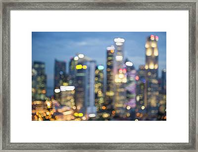 Blurred View Of City Skyline Lit Up At Framed Print by Jacobs Stock Photography Ltd