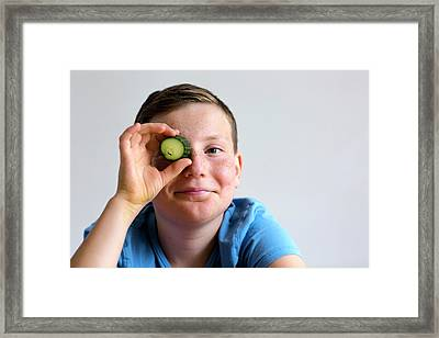 Boy Holding Cucumber Over Eye Framed Print by Gombert, Sigrid