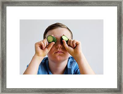 Boy Holding Cucumber Over Eyes Framed Print by Gombert, Sigrid