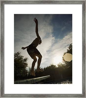 Boy Jumping Off Diving Board Framed Print by Kelly Redinger