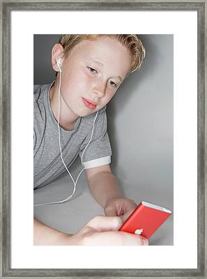 Boy Listening To Music Framed Print by Gustoimages/science Photo Library
