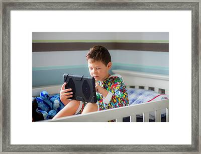 Boy Sitting In Bed Using A Digital Tablet Framed Print