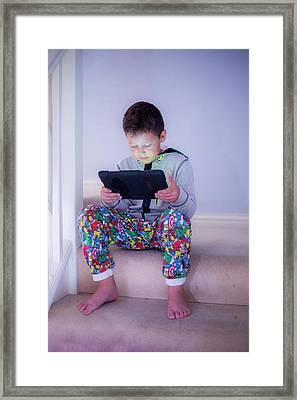 Boy Sitting On A Step Using A Tablet Framed Print