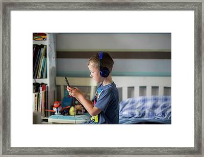 Boy Wearing Headphones Using Device Framed Print