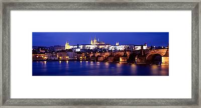 Bridge Across A River Lit Up At Night Framed Print