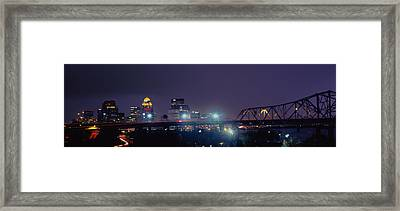 Bridge With Skyline Lit Up At Night Framed Print by Panoramic Images