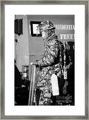 British Army Soldier In Riot Gear With Fire Extinguisher In Front Of Land Rover On Crumlin Road At A Framed Print by Joe Fox