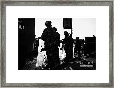 British Army Soldiers In Riot Gear With Shields Backlit Silhouette Beneath Protest Sign On Crumlin R Framed Print by Joe Fox