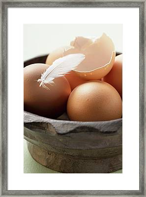 Brown Eggs, Eggshell And Feather In Wooden Bowl Framed Print