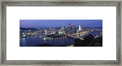 Buildings Along A River Lit Up At Dusk Framed Print by Panoramic Images
