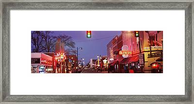 Buildings Along The Street Lit Framed Print by Panoramic Images