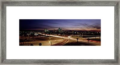 Buildings In A City Lit Up At Dusk, 7th Framed Print