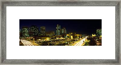 Buildings In A City Lit Up At Night Framed Print