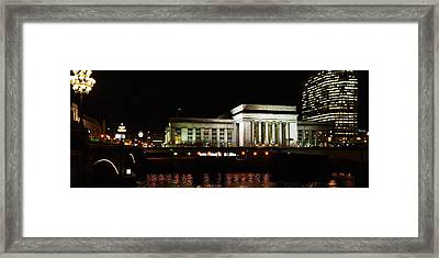 Buildings Lit Up At Night At A Railroad Framed Print by Panoramic Images