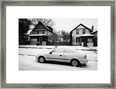 car covered in snow parked by the side of the street in front of residential homes caswell hill Sask Framed Print
