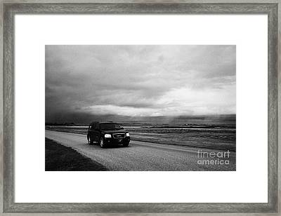 car driving on rural road as storm snow clouds forming over the prairies assiniboia Saskatchewan Can Framed Print