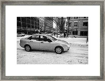 car travelling along snow covered city streets in Saskatoon Saskatchewan Canada Framed Print by Joe Fox