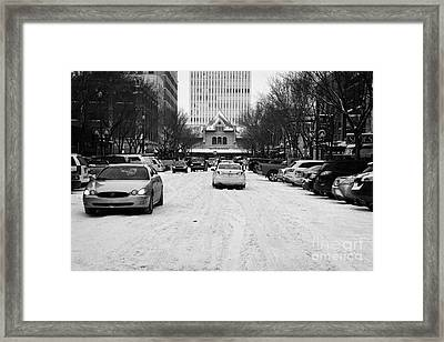 cars driving though snow covered streets in downtown Saskatoon Saskatchewan Canada Framed Print