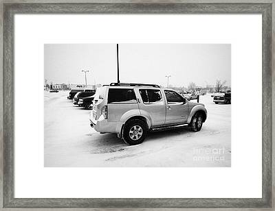 cars parked in store parking lot family reserved space in snowstorm blizzard Saskatoon Saskatchewan  Framed Print by Joe Fox