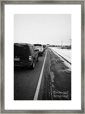 cars waiting on train crossing trans-canada highway in winter outside Yorkton Saskatchewan Canada Framed Print by Joe Fox