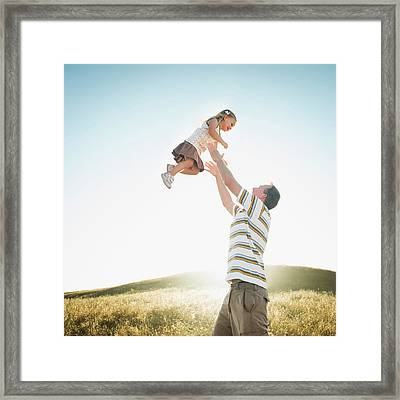 Caucasian Father Lifting Daughter Framed Print by Erik Isakson