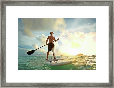 Caucasian Man On Paddle Board In Water Framed Print by Colin Anderson Productions Pty Ltd