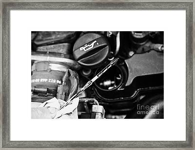 Checking The Oil Level On The Dipstick In A Car Engine Compartment Framed Print
