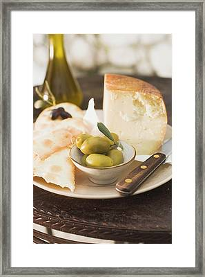 Cheese, Green Olives, Crackers And Olive Oil On Table Framed Print