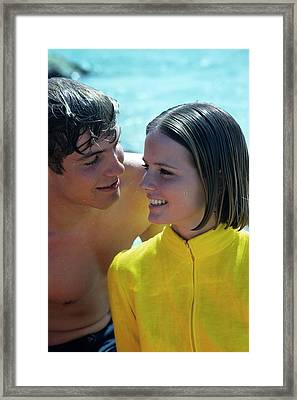 Cheryl Tiegs With A Male Model On A Beach Framed Print by William Connors
