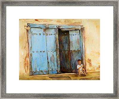 Child Sitting In Old Zanzibar Doorway Framed Print by Sher Nasser