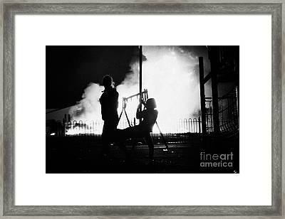 children play in playground at 11th night bonfire in Monkstown fire northern ireland Framed Print