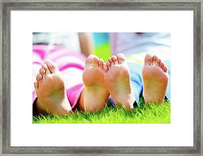Children Sitting On Grass With Bare Feet Framed Print