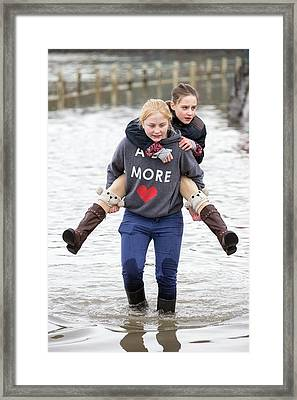 Children Wade Through Flood Waters Framed Print by Ashley Cooper