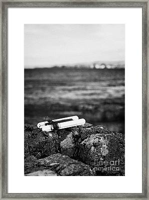 Childrens Bright Orange Crab Line Fishing Line With Weight Sitting On Rocks Near The Sea With Shoreline In Background Vertical Framed Print by Joe Fox
