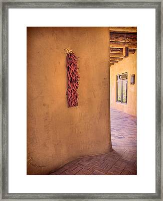 Chili Peppers On Adobe Wall Framed Print by Ann Powell