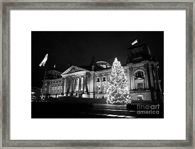 christmas tree and german flag flying fluttering on flagpole outside reichstag building Berlin Germany Framed Print by Joe Fox