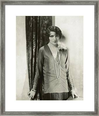 Claudette Colbert Standing By A Table Framed Print
