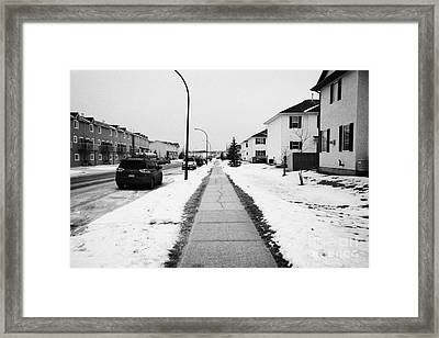 cleared salted gritted sidewalk in a residential development Saskatoon Saskatchewan Canada Framed Print by Joe Fox