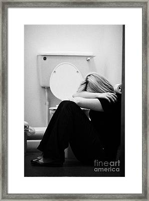 Close Up Of Arms And Shoulders Of Blonde Haired Teenage Woman Sitting In Fetal Position On Floor Of  Framed Print