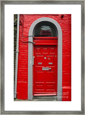 Colorful Red Door On Red Wall Framed Print